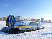 Nadym, Russia - March 15, 2008: The Soviet Snowmobile Arctic On The Background Of The City.