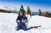 Smiling father in ski mask with son on shoulders