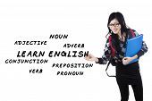stock photo of adverb  - Female student writes english language materials on whiteboard - JPG