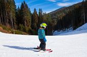 Small boy in ski mask standing and skiing