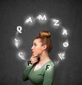 Thoughtful young woman with shining letters circulating around her head