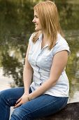 Young Woman Sitting On A Lakeshore