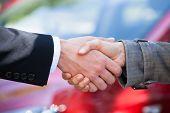 Car Dealer And Female Client Shaking Hands At Dealership