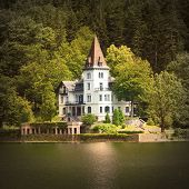 The Grundlsee lake coast with beautiful castle. Vintage style view from Salzkammergut in Austria, Eu