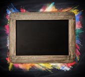 Wooden blackboard with free space for text, colored freeze motion of powder