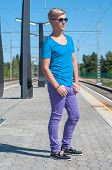 Stylish man  in blue standing on train station