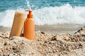 stock photo of suntanning  - hoto of suntan lotion bottles on the beach - JPG