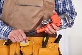 image of pipe wrench  - Midsection of male repairman with tool belt holding pipe wrench - JPG