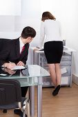 image of pervert  - Young pervert businessman looking at businesswoman working in office - JPG