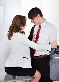 Businesswoman Undressing Male Colleague At Desk