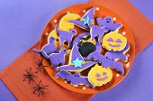 Happy Halloween Orange And Purple Sugar Cookies In Cat, Hat, Bat And Pumpkin Shapes On Orange And Pu