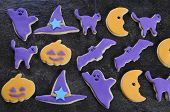 Happy Halloween Orange And Purple Sugar Cookies In Cat, Hat, Bat And Pumpkin Shapes On Black Slate K