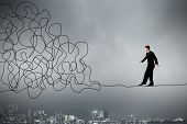 Businessman walking on twisted rope high in sky