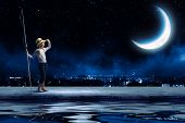 Cute girl at night with fishing rod looking far away
