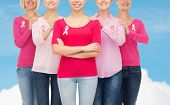 healthcare, people and medicine concept - close up of smiling women in blank shirts with pink breast cancer awareness ribbons over blue sky and white cloud background