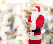 christmas, holidays and people concept - man in costume of santa claus with notepad and pen over lights background