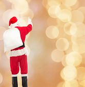 christmas, holidays and people concept - man in costume of santa claus with bag pointing finger from back over yellow lights background over beige lights background