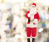 christmas, holidays and people concept - man in costume of santa claus over lights background