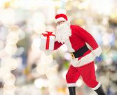 christmas, holidays and people concept - man in costume of santa claus running with gift box over lights background