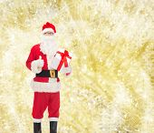 christmas, holidays and people concept - man in costume of santa claus with gift box showing thumbs up gesture over yellow lights background