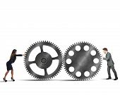 stock photo of interlock  - Businesspeople working together for perfect interlocking gears - JPG