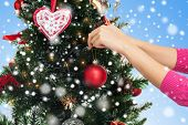 winter holidays, celebration and people concept - close up of woman hands decorating christmas tree with ball over blue background with snow