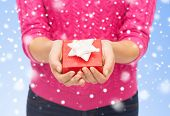 christmas, holidays and people concept - close up of woman in pink sweater holding small red gift box over blue background with snow over blue background with snow