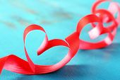 Ribbon shaped as hearts on color wooden background