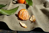 Juicy ripe tangerine with leaves on tablecloth