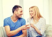 love, family, healthy food and happiness concept - smiling man giving cup of tea or coffee to wife or girlfriend at home