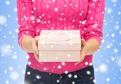 christmas, holidays and people concept - close up of woman in pink sweater holding gift box over blue background with snowover blue background with snow