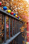 stock photo of ball cap  - Iron fence with multi colored decorative balls autumn scene - JPG