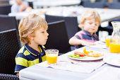 Two Little Kid Boys Having Healthy Breakfast In Hotel Restaurant Or City Cafe