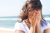 pic of humiliation  - a sad young woman covering her face on the beach - JPG