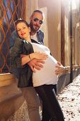 Pregnant couple posing in front of the window of an old villa