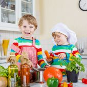 Two Cute Little Children Cooking Italian Soup And Meal With Fresh Vegetables