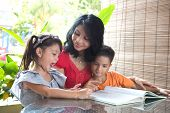Asian mother with young daughter and son reading a story book together in a home environment