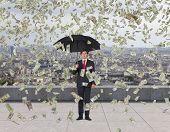 Businessman And Falling Dollar Bills