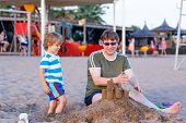 Happy Father And And Little Son Building Sand Castle On Sand Beach