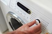 Close Up Of Man Choosing Cycle Program On Washing Machine