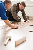 handymen laying laminate