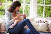 Mother At Home Cuddling Newborn Baby At Home