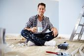 Portrait Of Man Decorating Nursery For New Baby