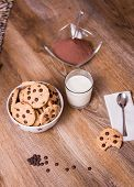 Chocolate chip cookies and milk on wood background