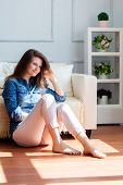 Young woman is sitting on the floor near the sofa