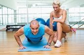 View of a female trainer assisting man with push ups at the gym