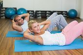 Side view of a fit couple doing abdominal crunches at the gym