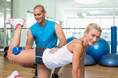 Side view of a male trainer assisting woman with exercises at fitness studio