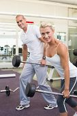 Portrait of a sporty young couple lifting barbells in the gym