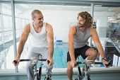 Portrait of fit young men working on exercise bikes at the gym